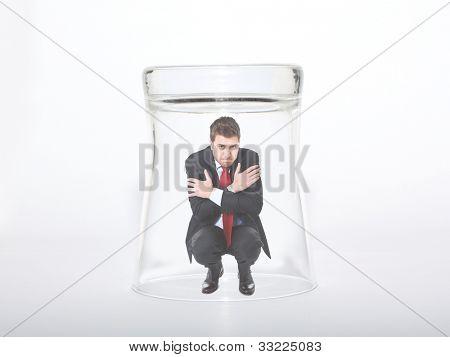 Businessman imprisoned under a glass