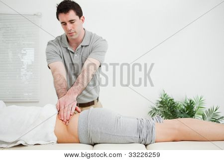 Masseur standing while massaging the back of his patient in a room