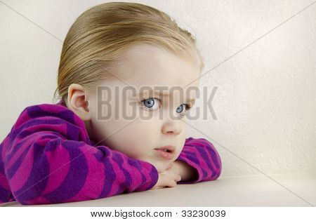 Cute  Young Girl Resting Her Head On A Table.