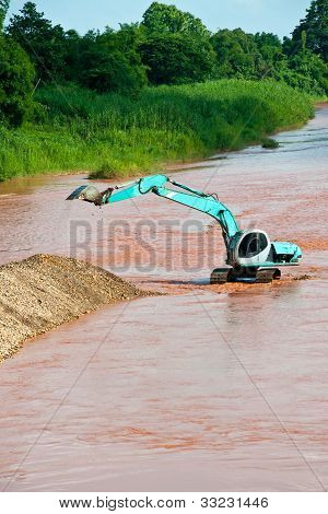 Excavator Loader At River With Raised Bucket Over Blue Sky