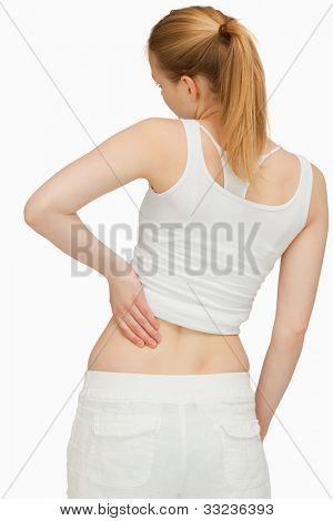 Young woman massaging her back against white background