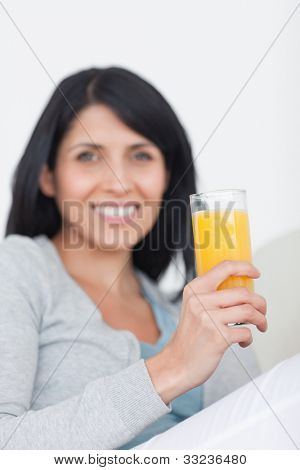 Woman smiling while holding a glass of orange juice in a living room