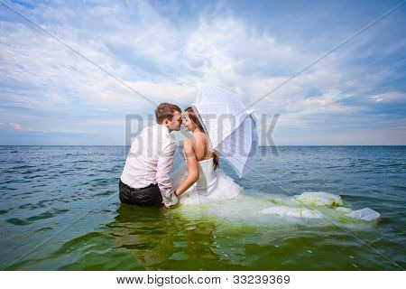 newlyweds couple sitting in water