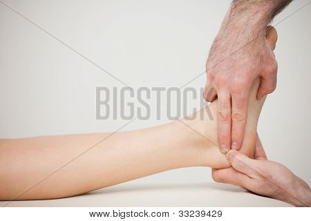 Chiropodist placing two fingers on a foot indoors