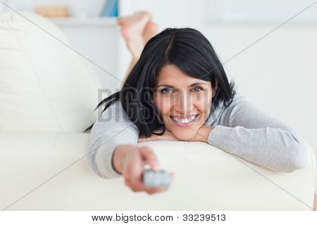 Woman pressing on a television remote while laying on a couch in a living room