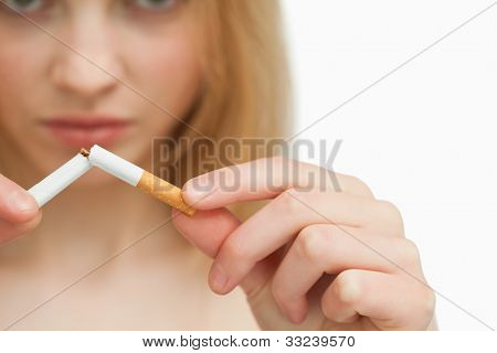 Close up of the hands of a woman breaking a cigarette against white background