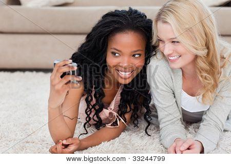 Eine junge Frau, die auf dem Boden liegend spricht ein Bild von sich selbst und ihre Freundin