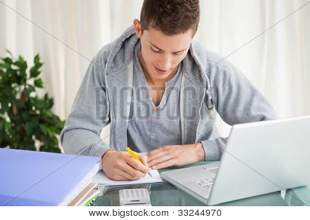 Smiling student doing his homework with a laptop on his desk