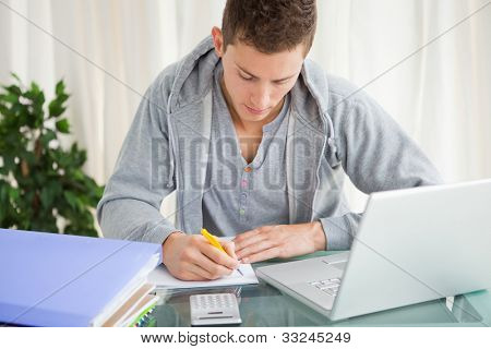 Student doing his homework with a laptop on his desk