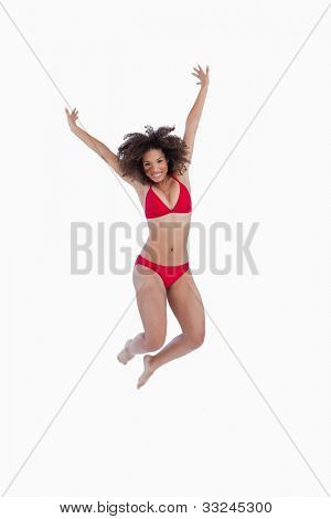 Happy brunette woman jumping while raising her arms against a white background