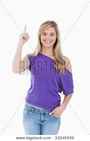 Smiling blonde woman raising her finger against a white background