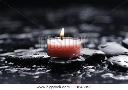 tranquil spa scene - burning spa candle with zen stones with water drops