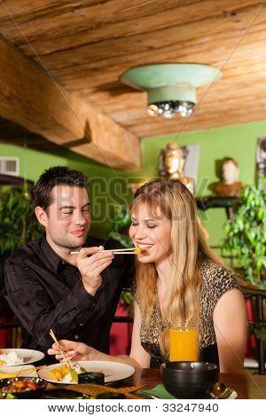 Junge Menschen, die in einem Thai-Restaurant, sie essen mit Stäbchen Essen