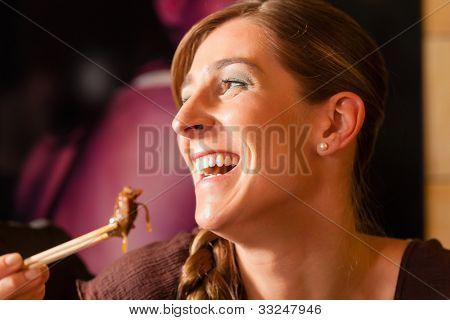 Junge Frau in einem thailändischen Restaurant Essen sie isst mit Stäbchen
