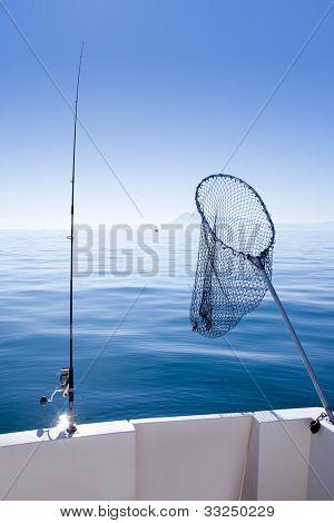 boat fishing rod and landing net in mediterranean blue sea