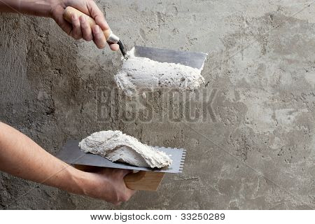 construction notched trowel and worker hands with white mortar on wall