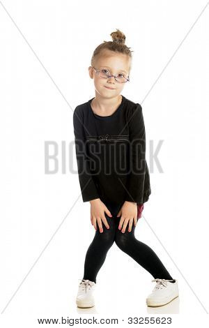 An adorable little girl with a tight bun and glasses down her nose goofing off with knock-kneed, pigeon toed stance.  On a white background.