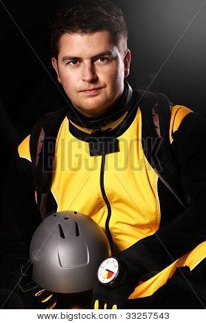 A picture of a young parachutist sitting over black background