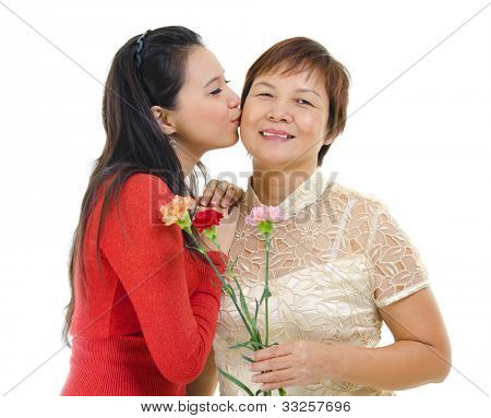 Mixed race asian daughter giving a kiss to her mum isolated on white