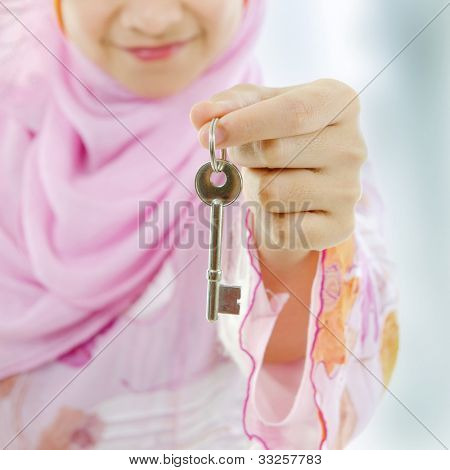 Muslim woman hand holding a new key