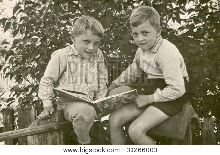 Vintage photo of brothers reading a book (sixties)