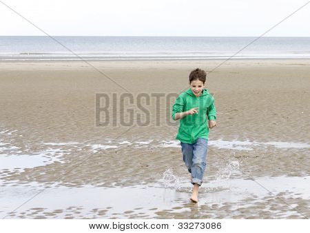 The Boy In A Green Hoodie, Running Barefoot On The Beach At Low Tide