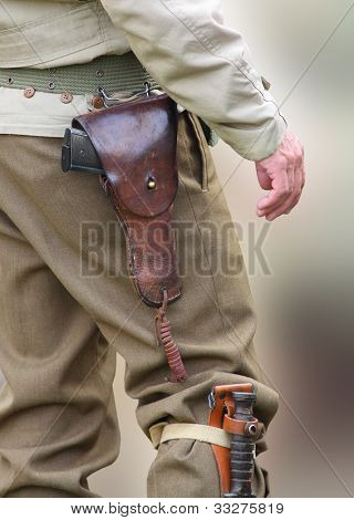 Armed american soldier preparing to shoot with his pistol. Vintage uniform from second world war. Close up with shallow DOF.