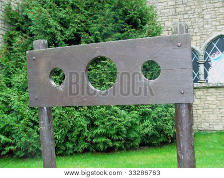 Some stocks stood in an English village by a church.