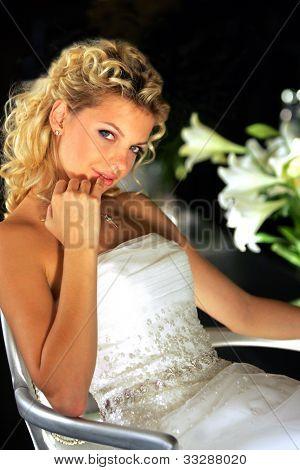 Retrato de cuerpo medio de novia rubia joven atractiva se sentó en la silla con fondo negro.