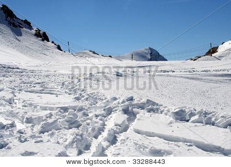 Closeup of ski tracks in snowy Alpine mountainous landscape.