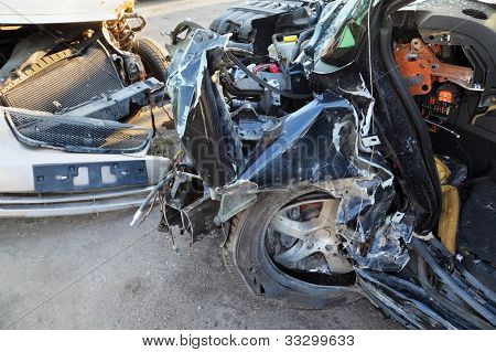 Crumpled and broken hoods of two collided cars after accident