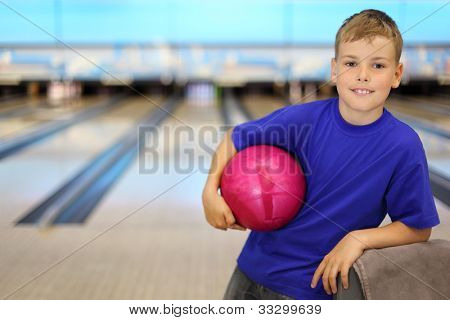 Happy boy dressed in blue T-shirt holds pink ball in bowling club; shallow depth of field