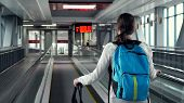 Young Woman Traveller On Escalator With Backpack And Suitcase In Airport Terminal. She Is Going To T poster
