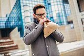 Businessman Holding Paper Bag Over Mouth As If Having A Panic Attack poster