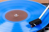 Close Up Of Turntable Needle On A Vinyl Record. Turntable Playing Vinyl. Needle On Rotating Blue Vin poster