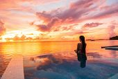 Paradise sunset idyllic vacation woman silhouette swimming in infinity pool looking at sky reflectio poster