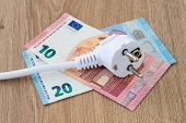 White Power Plug On Euro Banknotes Over A Brown Wooden Surface. Cost Of Electricity And Expensive En poster