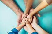 Closeup Of The United Hands Of One Family On A Blue Background. Dad, Mom, Kids Holding Hands. Large  poster