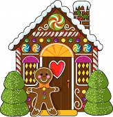 picture of gingerbread house  - A cute little decorated gingerbread house with a gingerbread man standing at the doorway - JPG