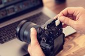 Photographer Inserting Or Removing A Memory Card In Professional Camera. poster