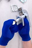 The Guy Holds In His Hands In Blue Gloves A Metal Matte Door Handle On A Light Background. Repair In poster