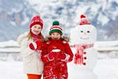 Child Building Snowman. Kids Build Snow Man. poster
