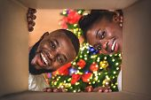 Magic Moments. Excited African American Couple Opening Christmas Present At Home, View From Inside O poster