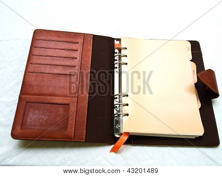 Opened Red-brown Organizer With A Pen