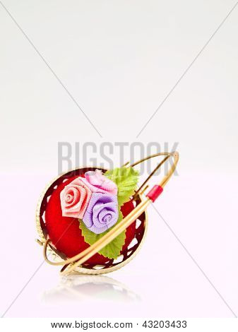 A Miniature Metalic Wicker Decorated By Roses On A Red Velvet Isolated On White Background