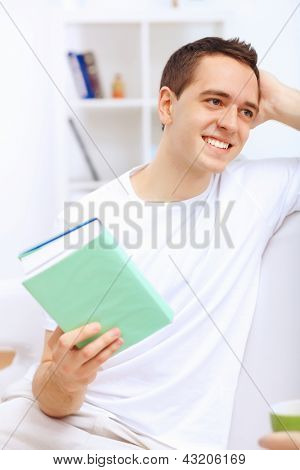 Young handsome man at home with a book