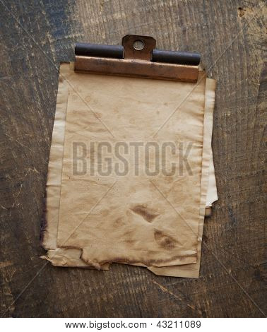 Very old sheets of memo paper with vintage copper clip, on old wood surface.