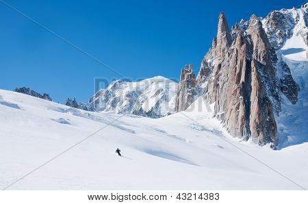 Skier goes downhill on a alpine glacier. In background the amazing panorama of the Mont Blanc peaks.Vallee Blanche, Chamonix, France.
