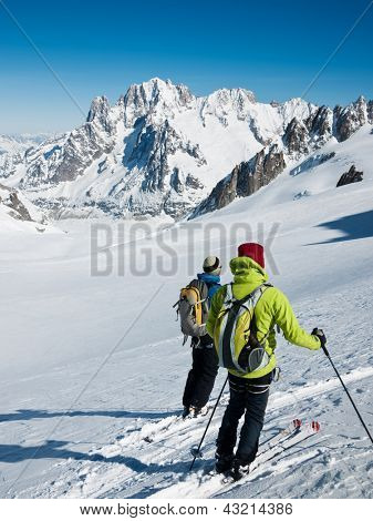 Two mountain touring skiers in front of the breathtaking view of Vallee Blanche and Aiguille Verte, Mont Blanc Massif, Western Alps, France, Europe.