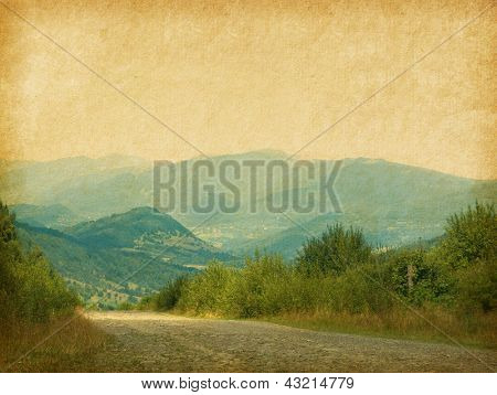 Country road in the mountains. Photo in retro style. Paper texture.